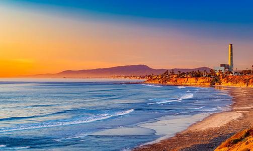 seashore under orange and blue sky