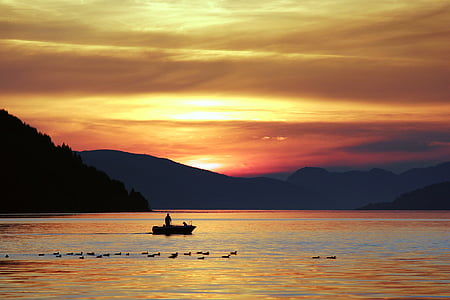 boat on the body of water during sunset