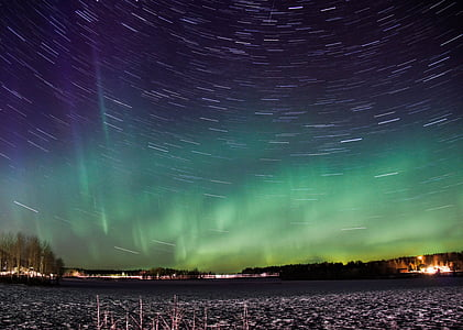 time-lapse photo of stars with aurora over the city