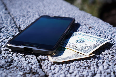 selective focus photographyt black Android smartphone and two 1 U.S. dollar banknotes