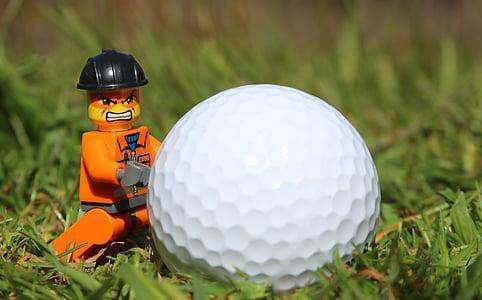 orange LEGO character minifig near golf ball