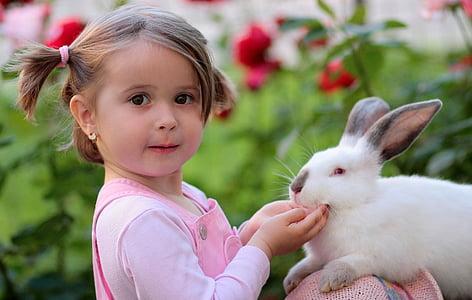 girl wearing pink dungarees holding white rabbit