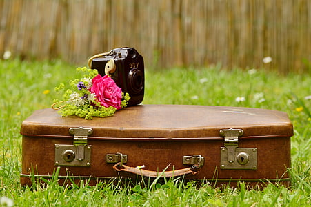black camera on top of brown leather suitcase