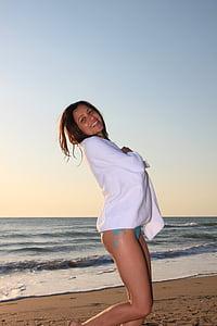 woman wearing teal bikini bottoms and white cardigan on beach