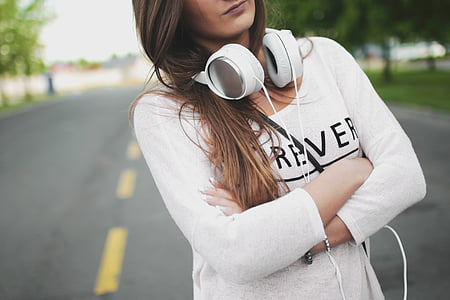 woman wearing white long-sleeved top with headphones