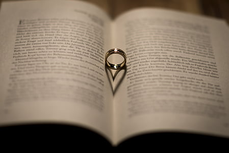 silver-colored ring on whit opened book