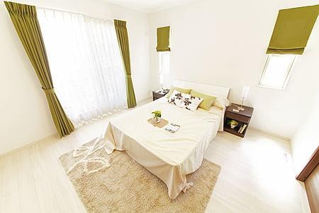bed with headboard and beige comforter in room