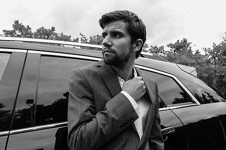 man in black suit beside car