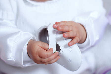 photo of baby holding white shoe