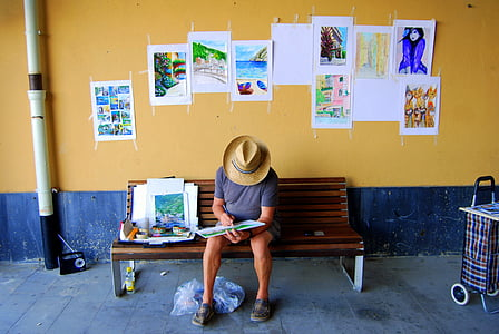 man reading book while sitting on bench near wall pasted with assorted paintings