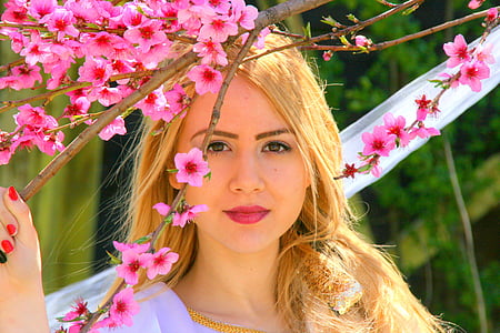 woman holding cherry blossom tree branch