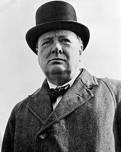 grayscale photograph of man wearing coat and hat