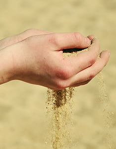 person holding brown sand at daytime