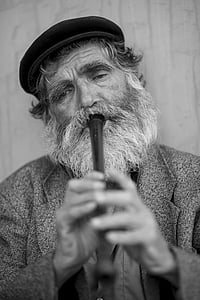 greyscale photo of bearded man playing flute