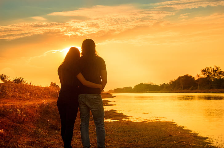 couple embracing each other looking on sunset