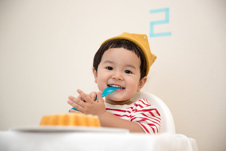 boy sitting on white plastic high-chair