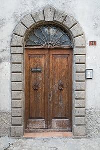 brown wooden closed door near doorbell at daytime