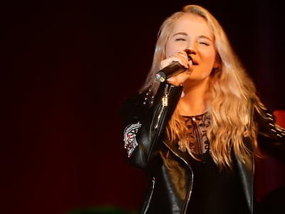 woman in black leather blazer singing