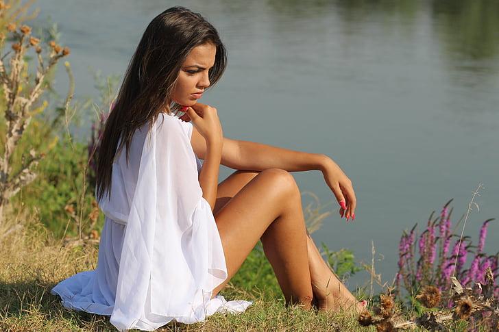 woman sitting on grass near river