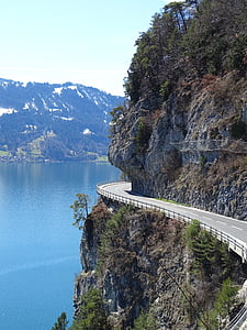 concrete road beside body of water