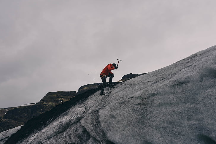 man holding pickaxe on gray rock