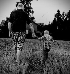 man holding boy walking on grass