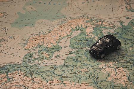 photo of black hatchback die-cast model on map