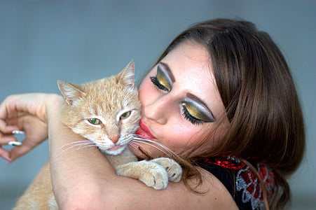 woman kissing orange tabby kitten