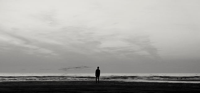 silhouette of person standing person near water