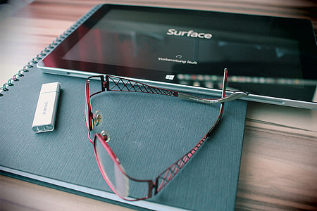 red framed eyeglasses near black Microsoft Surface Pro on top of table