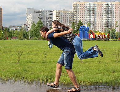 man carrying woman in his back while walking on water