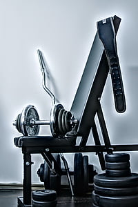 gray barbell and blue gym belt placed on black and gray exercise bench near wall