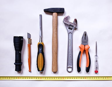 seven assorted-color handheld tools on white background
