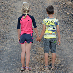 boy and girl holding hands during daytime