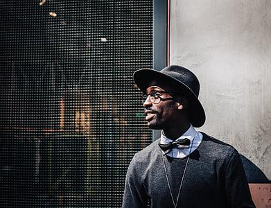 man wearing black fedora hat beside gray concrete wall
