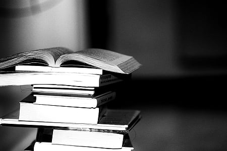 pile of books grayscale photography