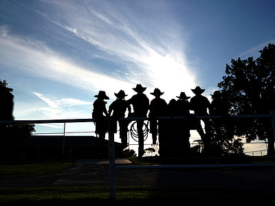 silhouette photo of men sitting the bridge