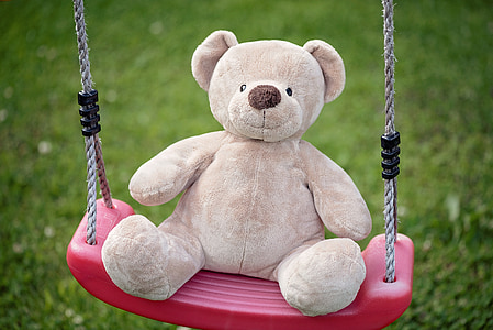 bear plush toy on pink swing