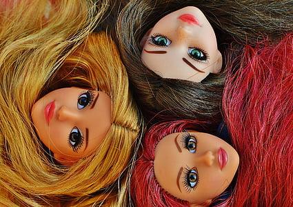 close-up photo of three girl dolls