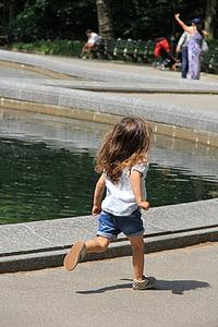 girl wearing white t-shirt runs beside pond at daytime