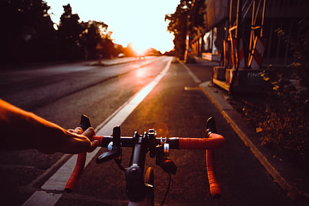 person riding on road bicycle during sunset
