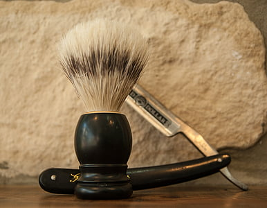 black and white shaving brush and black handled gray straight razor