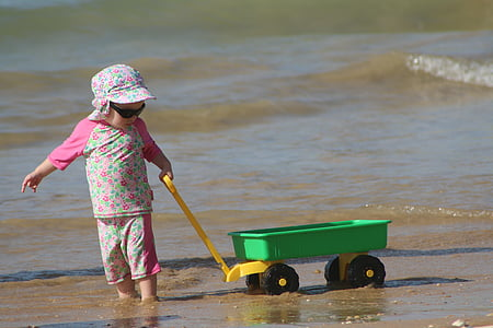 child pulling wagon on shore