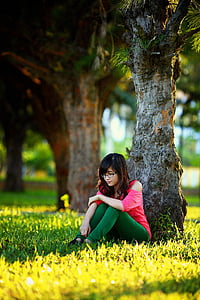 woman in pink cold-shoulder shirt and green leggings sitting under tree