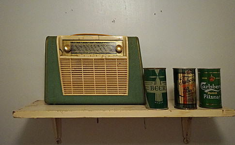 green and brown transistor radio beside three assorted cans