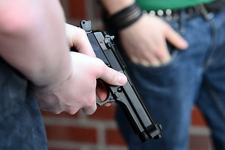 person holding black semi-automatic pistol