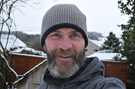 smiling man wearing gray knit hat outdoor