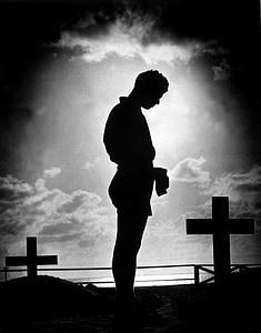 silhouette of man standing beside cross