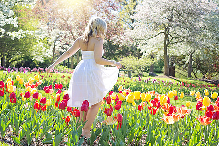 woman wearing white strapless dress standing on flower field during daytime