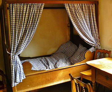 brown wooden panel bed with white and black curtain